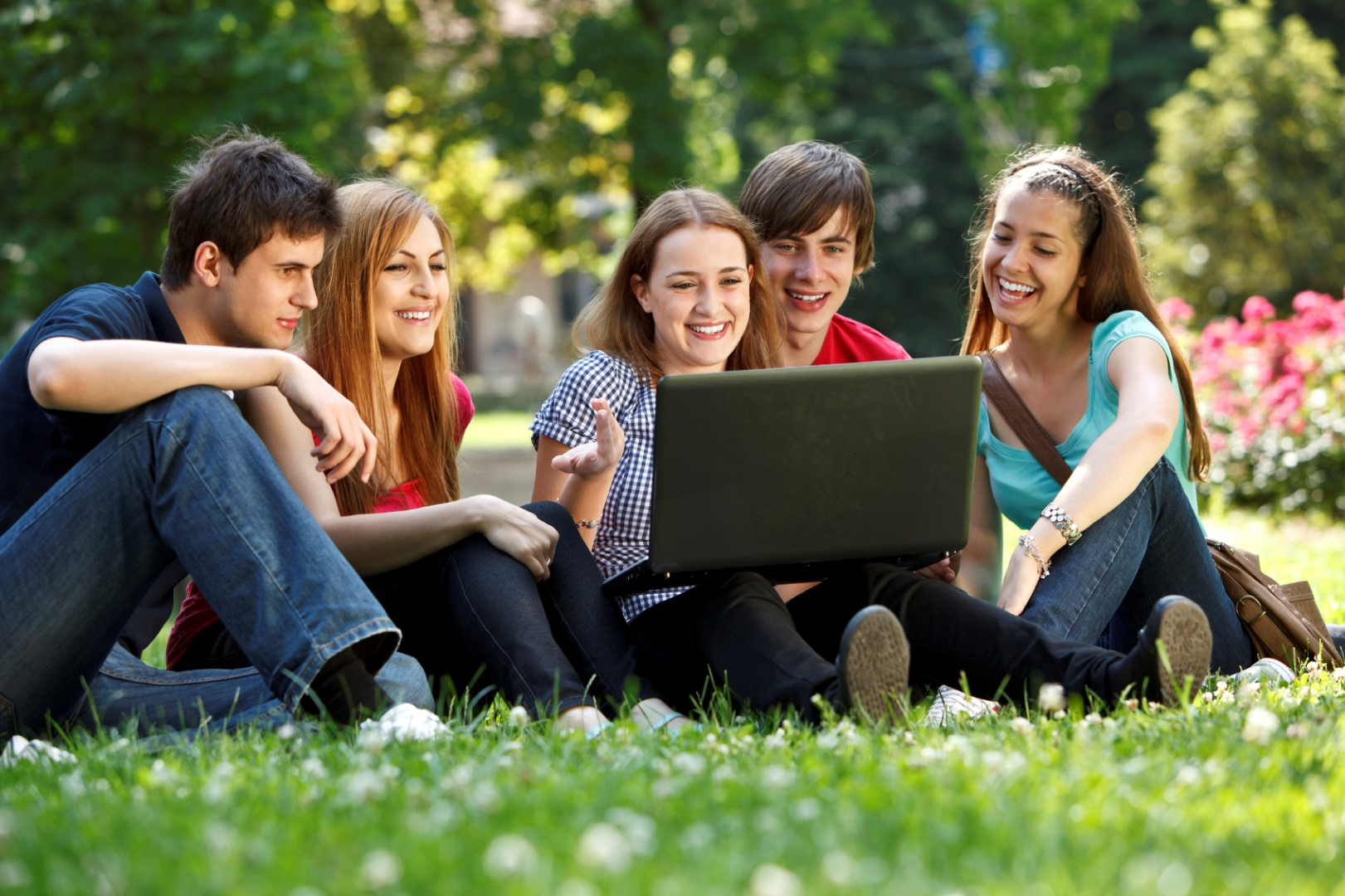 Group of college students using laptop outdoors